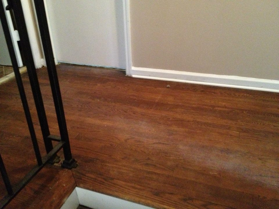 a wood floor before a Fabulous Floors refinishing